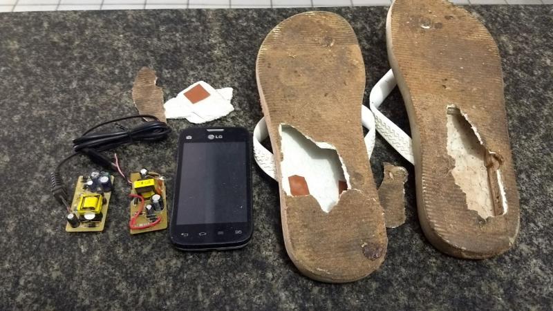 Homem é preso tentando entrar com celular em chinelo na Casa de Custódia