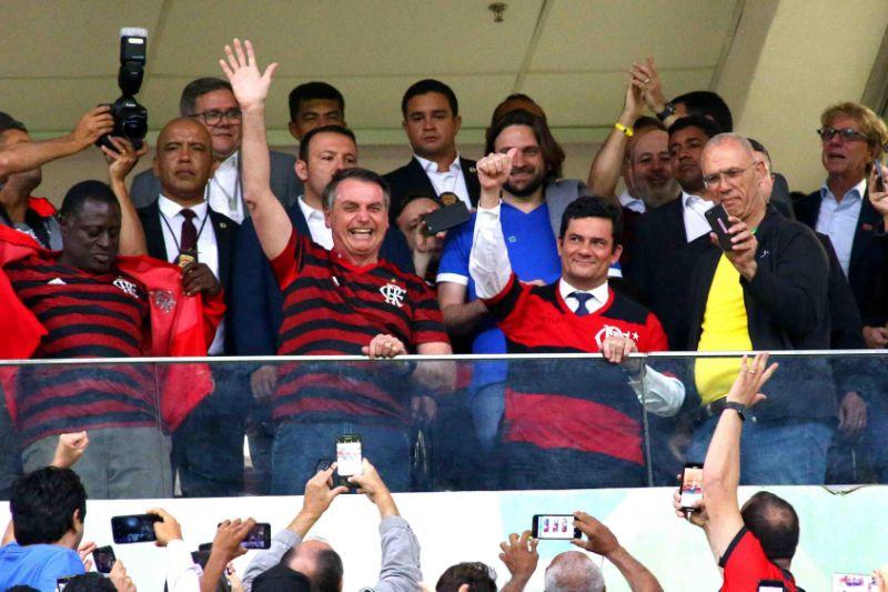 Bolsonaro e Sérgio Moro vão a estádio e vestem camisas de torcedores