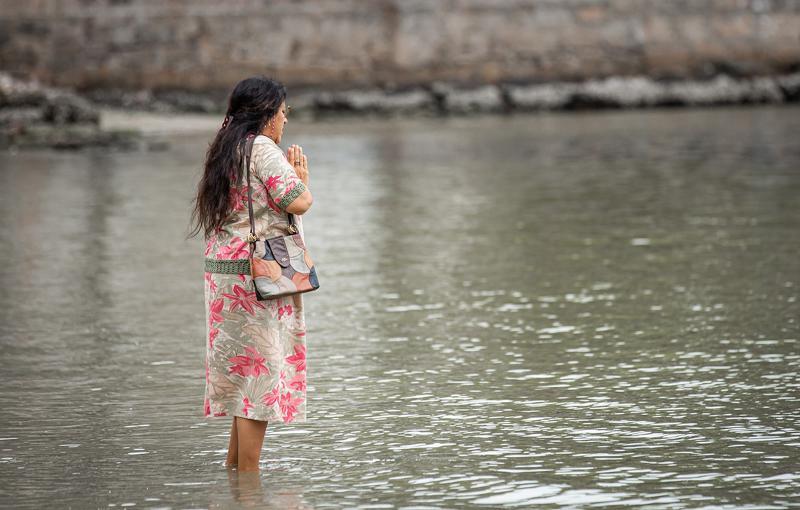 Em 'Amor de Mãe', Lurdes (Regina Casé) vai molhar os pés no mar e encontra pacotes de dinheiro — Foto: Artur Meninea/Gshow
